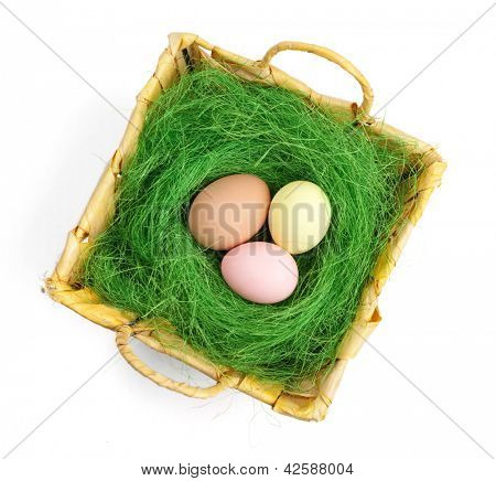 Colored easter eggs are in wattled basket with sisal green fibre, isolated on white