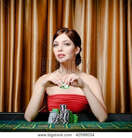 Portrait of female gambler sitting at the roulette table with chip in hand