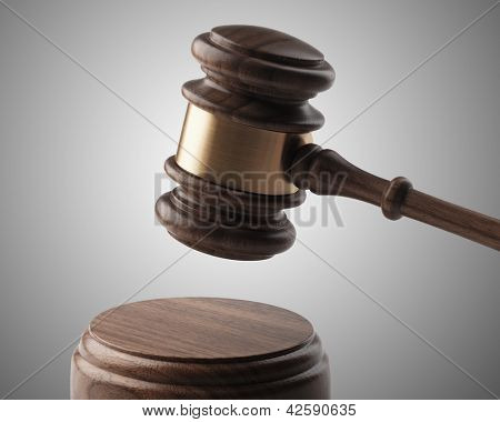 A wooden gavel and soundboard on a light grey background.