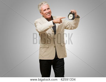 Man Pointing At An Alarm Clock against a grey background