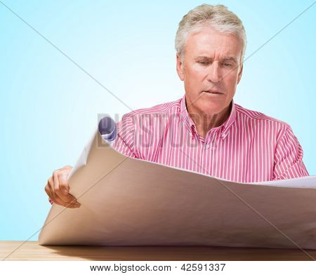 Mature Man Holding Blueprint against a blue background