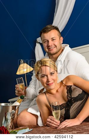 Intimate affair bed young couple drinking champagne woman nightgown