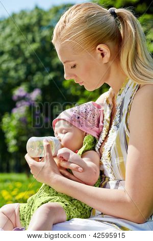 Young mother feeds her baby from bottle in spring park