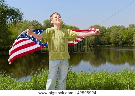 Boy in green t-shirt stands on bank of pond with eyes closed against the sun and holds unfolded flag behind his back
