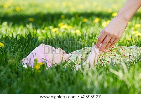 Baby lies on grass in spring park, mother hand touches him