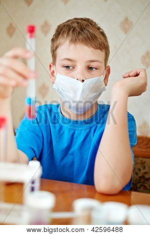 Boy in blue t-shirt sits at table with chemical reagents and looks at test tube, which he holds in his hand
