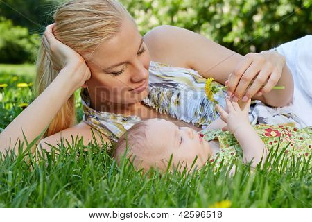 Smiling young mother reclines on green grass next to her baby daughter