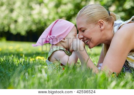 Young smiling mother and her baby-girl rub noses, sitting on grass in park