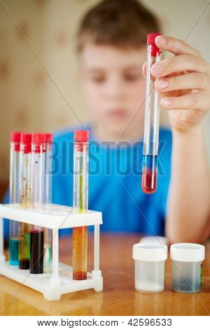Boy in blue t-shirt sits at table with chemical reagents and holds test tube in his hand, focus at fingers and tube