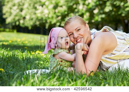 Young mother and her baby snuggle their cheeks, sitting on grass in spring park
