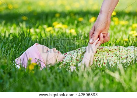Baby lies on grass in spring park, mother hand touches his hand