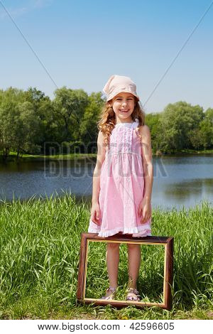 Girl stands in grass on bank of pond and picture frame is at her feet