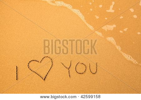 I Love You - text written by hand in sand on a beach, with a blue wave.
