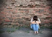 stock photo of disappointed  - Young woman in despair sitting against a brick wall - JPG