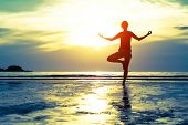 stock photo of  practices  - Woman practicing yoga on the beach at sunset - JPG