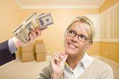 Постер, плакат: Женщина держащая карандаш передачи стек денег в пустой комнате с коробки