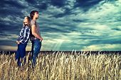 picture of hippies  - Romantic young couple in casual clothes standing together in a wheat field on a background of the storm sky - JPG
