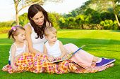 Photo of young mother with two cute kids reading book outdoors in spring time, happy mom teaching he