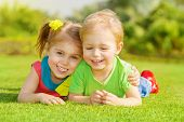 stock photo of grass  - Image of two happy children having fun in the park - JPG