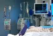 stock photo of icu  - ICU room in a hospital with medical equipments and a patient - JPG