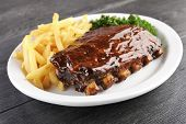 stock photo of ribs  - Grilled juicy barbecue pork ribs in a white plate with fries and parsley - JPG