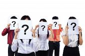 stock photo of candid  - Business colleagues holding question mark signs in front of their faces - JPG