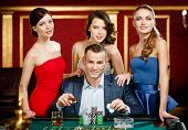 stock photo of roulette table  - Man surrounded by women gambles roulette at the casino club - JPG