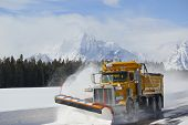 stock photo of plow  - Plow truck plowing snow in tetons park - JPG