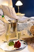 Champagne rose in bed celebrate special occasion hotel bedroom