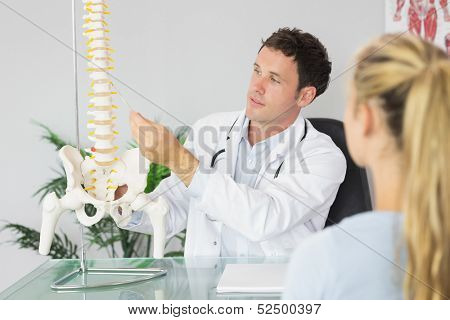 Content doctor showing a patient something on skeleton model in bright office
