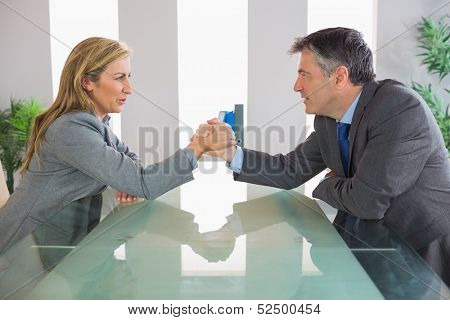Two irritated mature businesspeople having an arm wrestling sitting around a table at office