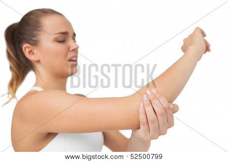 Suffering young woman touching her sore elbow on white background