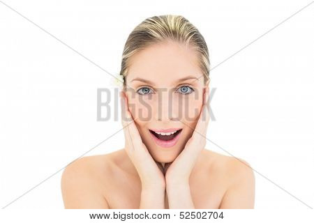 Astonished fresh blonde woman holding her head on white background