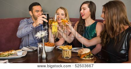 Friends having dinner together and clinking glasses in restaurant