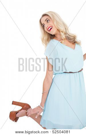 Smiling blonde model in blue dress posing and jumping on white background