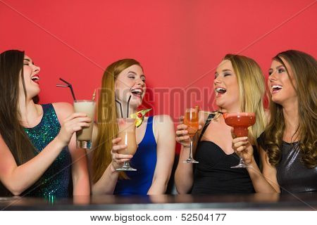 Laughing friends holding cocktails and chatting in a nightclub
