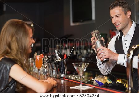 Handsome bartender serving cocktail to beautiful woman in a classy bar