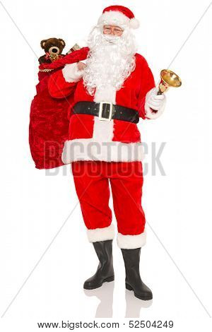 Santa Claus or Father Christmas carrying a sack full of gift wrapped presents and toys, isolated on a white background.