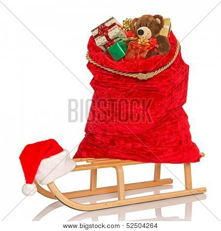 Santa's sack full of gift wrapped Christmas presents and toys including a handmade bear on a wooden sledge, isolated on a white background.