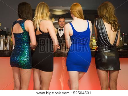 Attractive friends ordering drinks from barkeeper at nightclub
