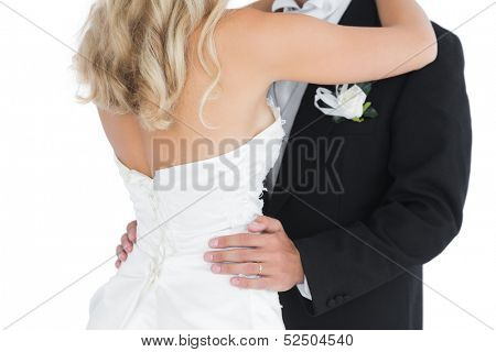 Mid section of a young dancing married couple on white background