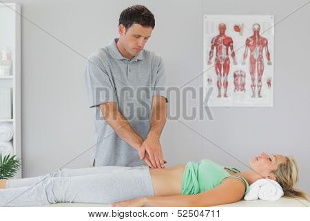 Physiotherapist examining patients pelvis in bright office