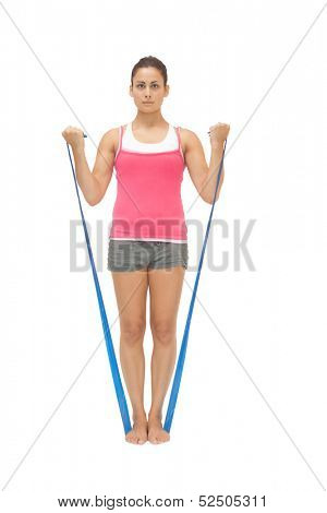 Stern sporty brunette exercising with resistance band on white background