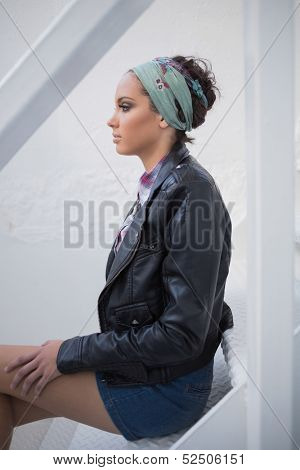 Side view of serious woman with hairband sitting on stairs