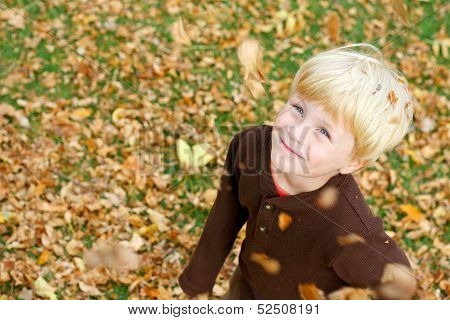 Happy Child Playing In Falling Leaves