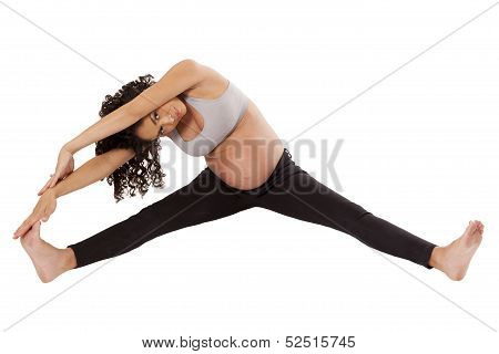 A Heavily Pregnant Woman Stretches Her Legs Before Exercise.