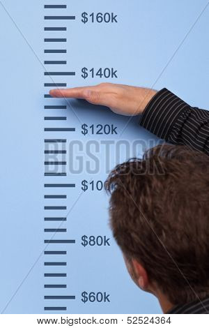 Businessman measuring dollar growth on a wall height chart