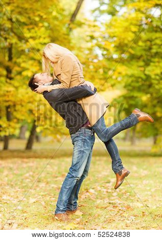 holidays, love, travel, tourism, relationship and dating concept - romantic couple playing in the autumn park
