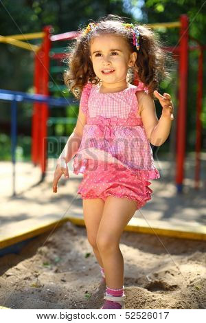 Little girl jumping into a sandbox