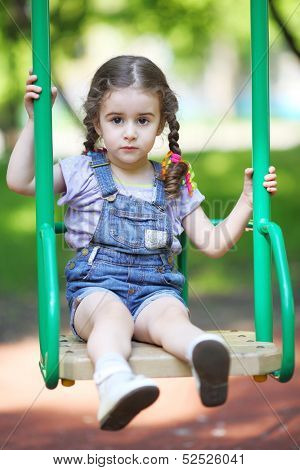 Little girl with pigtails sitting on a swing at the playground